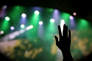 photodune-8018837-silhouette-hand-raised-at-concert-with-green-white-blue-stage-lights-s